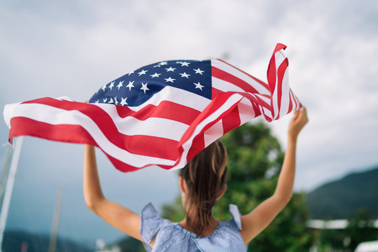 Child girl is waving American USA flag at background of the sea and yachts