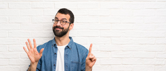Handsome man with beard over white brick wall counting six with fingers