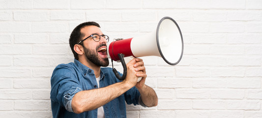 Handsome man with beard over white brick wall shouting through a megaphone