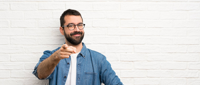 Handsome man with beard over white brick wall points finger at you with a confident expression