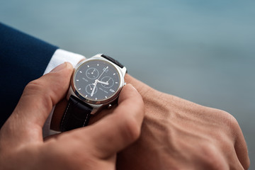 A man in a business suit checking a wrist watch on his hand on background  sea Wall mural