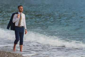 Businessman walking barefoot on the beach