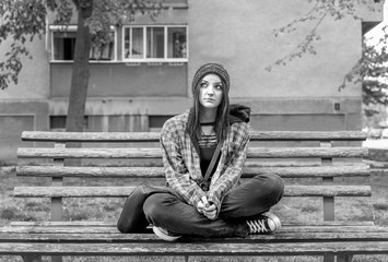 Young beautiful red hair girl sitting alone outdoors on the wooden bench on the street with hat and shirt feeling anxious and depressed after she became a homeless person black and white moody image