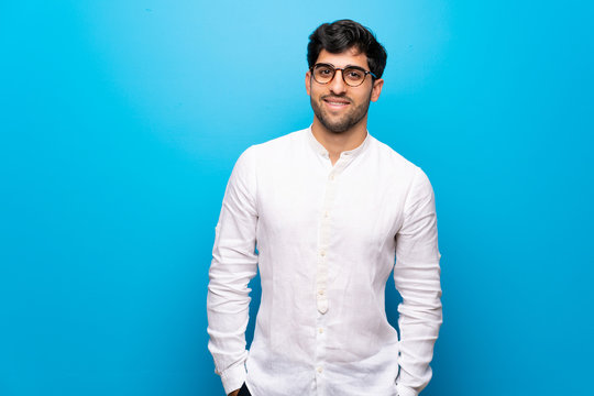 Young man over isolated blue wall with glasses and happy