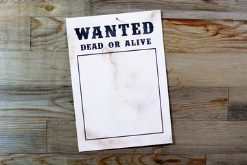 Wanted poster in front of wooden wall with copy space for own picture as a wanted photo