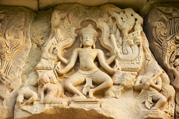 Sandstone carving with religious motifs at the ruins of the Hindu temple in Phimai historical park (Prasat Hin Phimai) in Thailand.