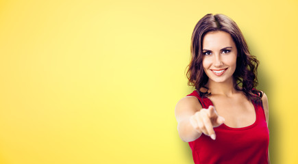 Photo of beautiful woman showing at you, over grey background