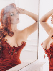 portrait of glamorous red-haired woman looking at herself in the mirror