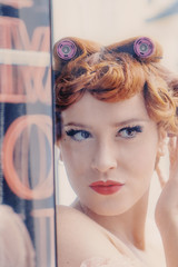 Young red-haired woman with rollers in hair pin-up retro style