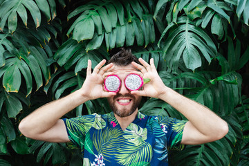 Young bearded man holding slices of Pitaya dragon fruit in front of his eyes, laughing