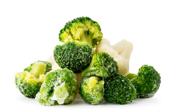 Heap of frozen broccoli and cauliflower close-up on a white. Isolated.