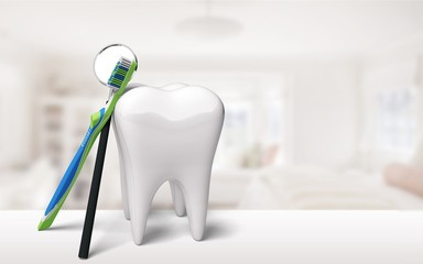 Big tooth model and toothbrush on background