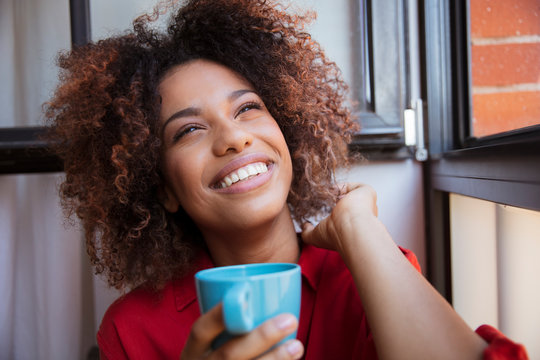 Young afro american woman relaxing with tea at home.
