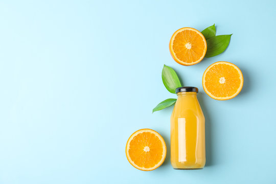 Flat lay composition with fresh orange juice in bottle and oranges with leaves on color background, space for text. Fresh natural drink