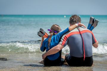 Fototapeta tata z córką odpoczywają na plaży po nurkowaniu w morzu obraz