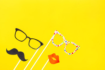 Props for party. Party, carnival paper accessories on the yellow background. Paper glasses, moustaches, lips, hat on stick. Men's and female image, flat-lay, top view.