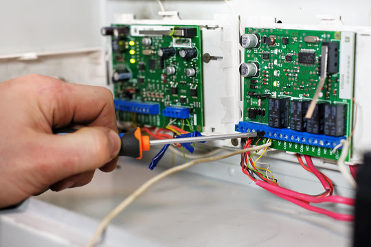 The mechanic on control and measuring devices makes repair and adjustment of the equipment. The hand of the worker with the screwdriver and the security chip, closeup