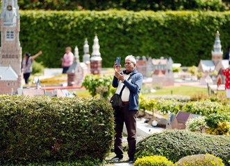 A tourist takes a picture with his phone at the Mini-Europe miniature park in Brussels