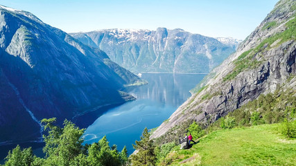 A couple standing on the meadow with a majestic view on Eidfjord from Kjeasen, Norway. Slopes of the mountains are overgrown with lush green grass. Water has dark blue color. Sunny and clear day Wall mural