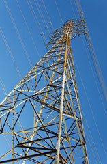 High voltage pylon against blue sky