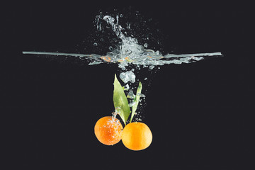 Mandarins with leaves thrown into water on dark background