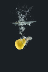 Yellow pear falling into water