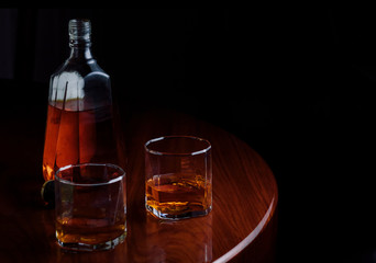 Glasses of whisky and bottle on wooden table