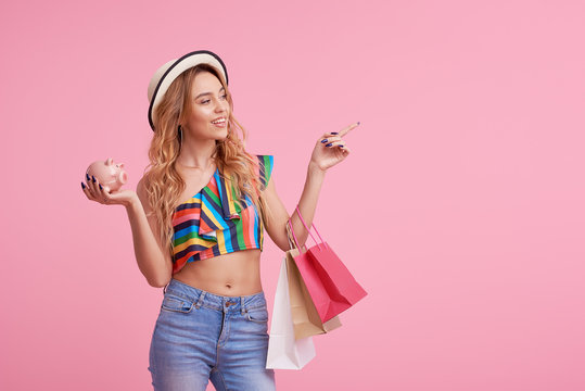 Sale concept. Portrait of a happy pretty girl in stylish hat holding shopping bags and Piggy bank. Looking at camera isolated over pink background. Pointing to the right