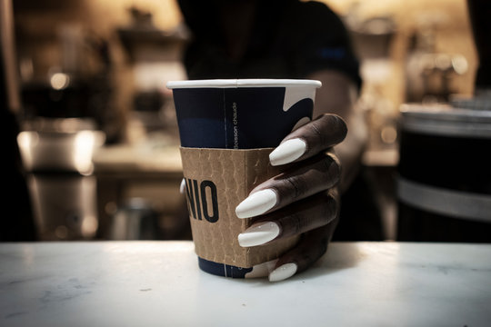 A woman with long nails holds onto a coffee cup.