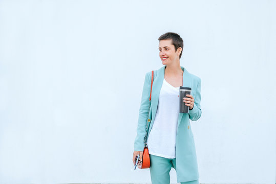 Woman in suit jacket holding thermo mug and mobile phone, white background
