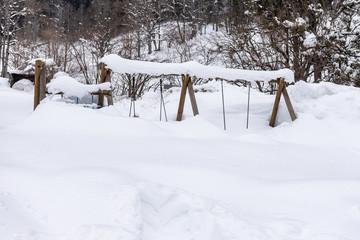 Children's playground in winter under the snow in mountain landscape.