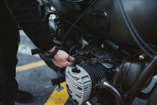 Anonymous male fixing engine of motorbike on parking lot on city street