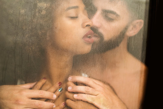 Handsome Hispanic guy touching and kissing seductive African American woman in lace bra while standing behind wet window at home