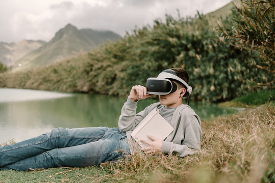 Young adolescent with virtual reality glasses laying on grass outdoors near a lake with a book