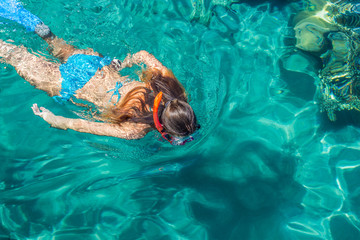 swimming girl in bright colorful aquamarine water of Gulf of Aqaba in Red sea, summer vacation and activities concept wallpaper pattern picture with empty copy space for text or inscription