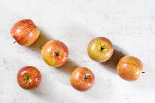 Tabletop view, six shiny apples (kiku variety) on white working board