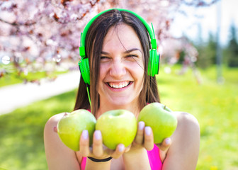 Young active woman holding green apple