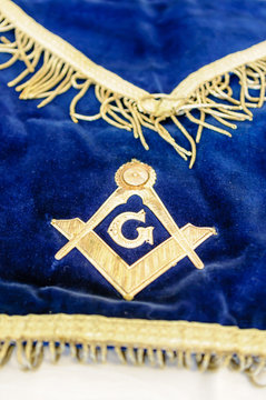 """Masonic symbol of Set Square, pair of compasses, and the letter """"G"""" on a ceremonial apron"""