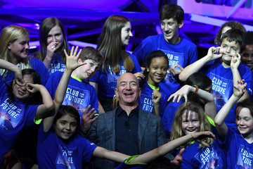 Founder, Chairman, CEO and President of Amazon Jeff Bezos poses with children from 'Club for the Future' after his space company Blue Origin's space exploration lunar lander rocket called Blue Moon was unveiled at an event in Washington