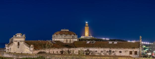 Fotografía nocturna de la cárcel de A Coruña con la Torre de Hércules de fondo iluminada.