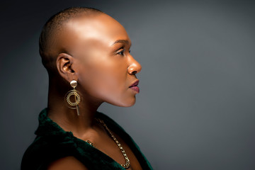 Black African American female fashion model with a bald hairstyle in a studio.  The portrait shows the beauty and confidence of the bold and trendy glamour hairdo style.
