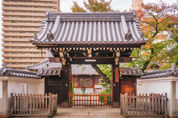Traditional Japanese Gate with intricate timber details and specific Japanese roof structure at a Buddhist temple in Nakadera, Chuo Ward, downtown Osaka, Japan.