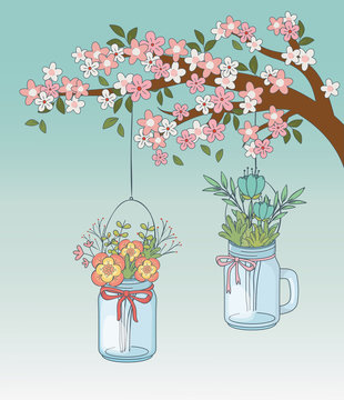 mason jars with flower hanging in tree branch
