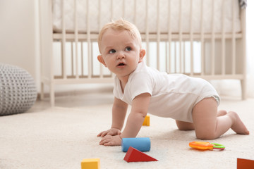 Cute little baby crawling on carpet indoors Wall mural