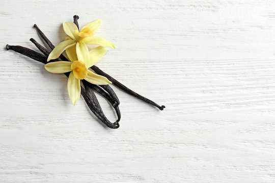 Flat lay composition with vanilla sticks and flowers on wooden background. Space for text