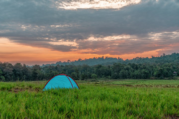 landscape scenery of camping tent on grass field with background of forest and mountains and sunrising sky in natural park