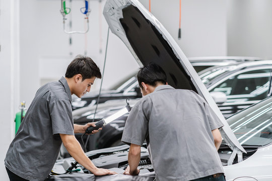 Asian mechanics open the car hood and checking the engine at maintainance service center for in showroom
