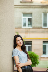 8b458672c3 cute young girl posing near building. sweet woman in a gray T-shirt ...
