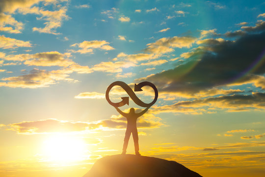 A silhouette of a man holds an infinity symbol on top of a mountain with a sunset background. Concept idea, life, success, business.