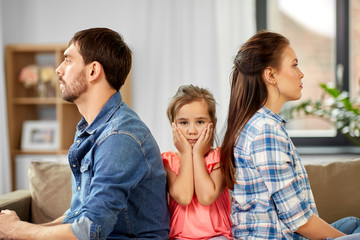 family problem, divorce and people concept - unhappy father, mother and sad little daughter at home